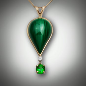Pendant 159A Malachite is a balloon pendant with the inlay of malachite and a 3 point F/VS diamond with a dangling 5.5 by 4.5mm oval tsavorite garnet set in 14kt yellow gold.