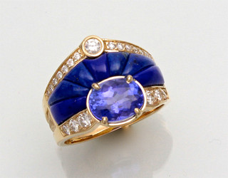 This custom R-1056 has a oval tanzanite as the center stone and F/VS pave` diamonds with hand carved lapis all set in 14kt yellow gold.