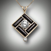 Pendant 238 has a center stone 8.5mm renzite with a 10 point F/VS diamond on the bottom the inlay stone is hand carved black jade and it is set in 14 karat yellow gold.