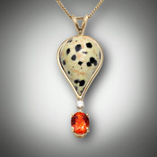Pnd 159-A Dalmatian Poppy pendant has a 7 by 5mm oval spessartite garnet, a 3 point F/VS pave` diamond and the hand carved inlay stone is dalmation poppy jasper which is set in a 14kt yellow gold frame.