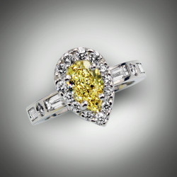 R 1223 this women's ring has a 1.05 ct fancy deep yellow color and SI1 clarity pear shape diamond.   The center stone is surrounded by a halo of  F/VS pave` round diamonds of 18 points and the shank has 3.4 points F/VS round diamonds and 0.32 points baguettes set in 18kt white gold.
