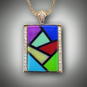 PND 433 is a beautiful Mondrian style pendant in 14kt Yellow Gold with .84 points of F/VS pave diamonds, featuring hand sculpted Turquoise, Gaspeite, Variscite, Red Fairy Jasper, Lapis, Sugilite, Verde Antique marble and Black Jade on a 14kt Yellow Gold wheat chain.
