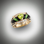 R 801 has a 6.5mm trillion cut peridot for the center with 20 points of F/VS pave` diamonds and hand carved black jade and gaspeite for the inlay stones all set in 14kt yellow gold.