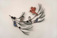 Hand carved wooden birds on metal pine tree branch with small pine cones.