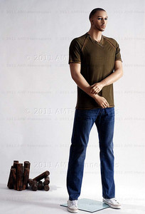 In this full body side view photo, wearing a casual olive-green t-shirt and jeans with shoes,  mannequin Bill, stands with his legs even, his arms raised to his waist with his left hand almost touching his right arm.  Mannequin Bill can be displayed with or without a wig / hairpiece.  Glass stand and support hardware included.