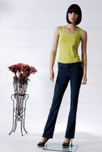 In this full body view, wearing a short dark brunette wig, fitted black pants and casual green top, mannequin Echoe stands with her left hip slighly lifted and her hans almost straight down at her sides.  Her right foot is slightly forward.   With pierced ears, she can display earrings and jewelry.  Glass stand and support hardware included.