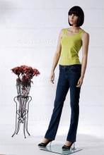 In this full body side view, wearing a short dark brunette wig, fitted black pants and casual green top, mannequin Echoe stands with her left hip slighly lifted and her hans almost straight down at her sides.  Her right foot is slightly forward.   With pierced ears, she can display earrings and jewelry.  Glass stand and support hardware included.