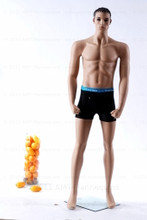 In this full body view photo, wearing a black swim suit, mannequin Mike, stands with his left light slighly forward with his arms straight at his sides - hands in fists.  Mannequin Mike can be displayed with or without a wig / hairpiece.  Glass stand and support hardware included.