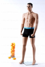 In this full body side view photo, wearing a black swim suit, mannequin Mike, stands with his left light slighly forward with his arms straight at his sides - hands in fists.  Mannequin Mike can be displayed with or without a wig / hairpiece.  Glass stand and support hardware included.
