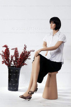In this full body side view, wearing a short dark brunette wig, a white blouse and black skirt, mannequin Emily sits with her right leg crossed over her left and her left hand resting on her right knee. Her right hand is at her waist.   With pierced ears, mannequin Emily can display earrings and jewelry.  Pedestal included.