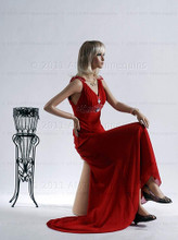 In this full body side view, wearing a shoulder length blond wig and a long, red formal dress, mannequin Emily sits with her right leg crossed over her left and her left hand resting on her right knee. Her right hand is at her waist.   With pierced ears, mannequin Emily can display earrings and jewelry.  Pedestal included.