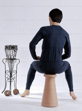 In this full body view rear photo, wearing a short dark brunette wig / hairpiece and a tight black workout suit,  mannequin Roger sits upright with his legs apart and his hands in his lap.  Mannequin Roger can be displayed with or without a wig / hairpiece.  Pedestal included.