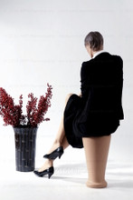 In this full body rear view, wearing a black business suit with a white blouse and heels, mannequin Ruby sits with her right leg crossed over her left and her right hand resting on her right knee. Her left hand rests on her left knee.   With pierced ears, mannequin Ruby can display earrings and jewelry.  Pedestal included.
