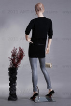 In this rear full body view photo, mannequin Betty displays cutting-edge grey leather pants with a belted soft knit black top.  She stands in a neutral stance with her right leg slightly forward.  Her left arm is bent with her hand resting above her waist while her right arm is almost straight down with her hand at hip level.  With pierced ears, mannequin Betty can display earrings and jewelry.  Glass stand and support hardware included.