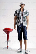 In this full body view photo, wearing a a casual open plaid shirt  with long shorts and deck shoes, mannequin Jim, stands with his left foot slightly forward his hips slightly angled with his arms straight down.  Mannequin Jim can be displayed with or without a wig / hairpiece.  Glass stand and support hardware included.