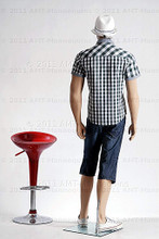 In this full body rear view photo, wearing a a casual open plaid shirt  with long shorts and deck shoes, mannequin Jim, stands with his left foot slightly forward his hips slightly angled with his arms straight down.  Mannequin Jim can be displayed with or without a wig / hairpiece.  Glass stand and support hardware included.