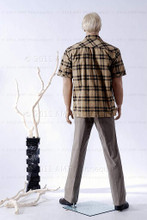 In this full body rear view photo, wearing a short blond wig / hairpiece, grey slacks, black loafers, and a tan plaid shirt, mannequin Ed, stands with his legs apart in even stance with his arms straight at his sides.  Mannequin Ed can be displayed with or without a wig / hairpiece.  Glass stand and support hardware included.