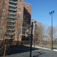 Queens Middle School outdoor basketball court with round tapered steel anchor base light poles, steel bullhorn brackets, and LED Shoebox light fixutres.