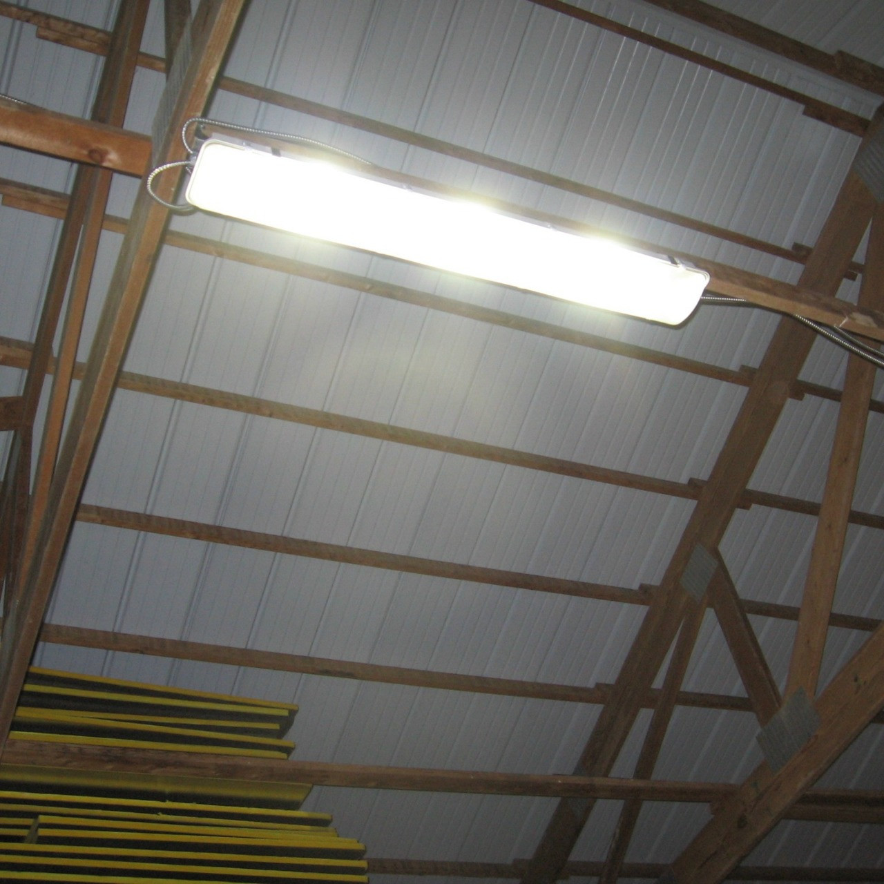 Light fixtures made in usa 80w led low bay light fixtures mounted on the beams of the lumber warehouse