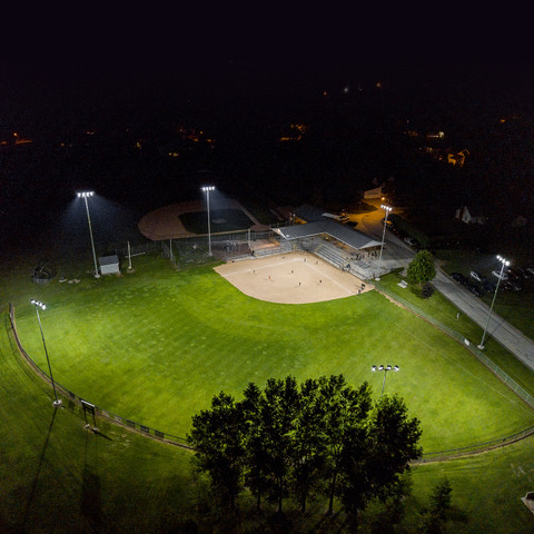 Complete LED sports lighting package including LED Helios fixtures, custom steel sports poles, brackets, and Glare Killer systems.