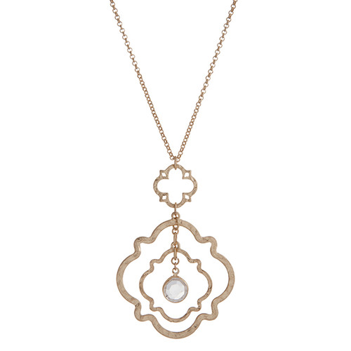"Worn gold tone layering linked quatrefoil with a dangling clear glass stone. Approximately 30"" in length."