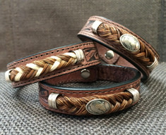 "From Cowboy Collectibles these tooled leather bracelets feature classic western styling. Accented with sterling silver findings and braided horsehair, these bracelets are secured with a snap closure.  Bracelets come gift boxed and are available in Small - 7 1/8"" Medium - 8""  Cowboy Collectible products are handmade in Montana, USA."