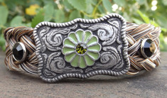 "Flower Buckle Bracelets by Cowboy Collectibles Buckles and bling! These bracelets feature a buckle-shaped concho with flower and rhinestone accents. Attached to a 3/4"" wide leather band with snap closure and finished with metal end caps is a basket-weave style horse hair braid.  Gift boxed.  Horse Hair will range in color from Sorrel, Chestnut, Granite, Grey, Black, etc.  Available in three sizes. Small - 7"" Medium - 8"" Large - 9""."
