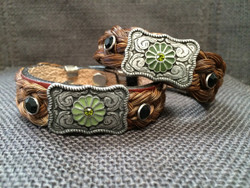 """Flower Buckle Bracelets by Cowboy Collectibles Buckles and bling! These bracelets feature a buckle-shaped concho with flower and rhinestone accents. Attached to a 3/4"""" wide leather band with snap closure and finished with metal end caps is a basket-weave style horse hair braid.  Gift boxed.  Horse Hair will range in color from Sorrel, Chestnut, Granite, Grey, Black, etc.  Available in three sizes. Small - 7"""" Medium - 8"""" Large - 9""""."""