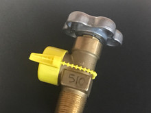This cap has a strap that wraps around the valve.  The strap must be broken to remove the cap.