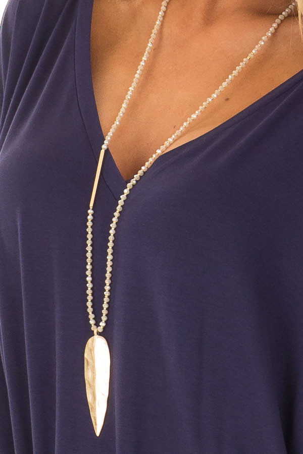 Beige Beaded Necklace with Gold Leaf Pendant close up