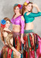 three women posing, wearing akhet holographic lycra mock wrap top featuring golden, pink, and green colors