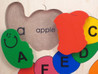 "Alphabet ABC Wooden Puzzle closeup detail of Capital and lowercase ""A"" and ""apple""."