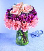 Pretty petals in a tiered design make a unique bouquet. Pink carnations form the first tier; deep lavender alstroemeria fill the center, and three luscious pink roses are the crowning touch. A stylish design for anyone who appreciates something above the ordinary.