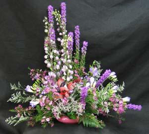 "As close to, "" thistles "" as we can get, Liatris , Statice, Limonium, and Delphinium complete this purple and mauve table arrangement. A Tartan bow finishes this tribute to a "" Scot ."" hatcher Florist can delivery this arrangement for you."