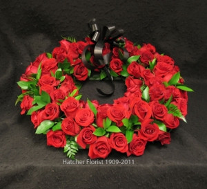 Red Freedom roses, Italian ruscus and a black bow accent this splendid wreath. This is an oroiginal by Hatcher florist. We can deliver to local Toronto, North York, Thornhill, Richmondhill and area funeral home. other colours available but a higher price. Very close to Jerrett, Kane, York Visitation and Simple Alternative funeral homes.