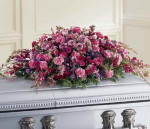 An abundance of purple flowers are lavished upon this casket spray to convey your affection.