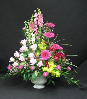 A beautiful pink and green arrangement featuring green cymbidium orchids, pink roses and larkspur or snapdragons.