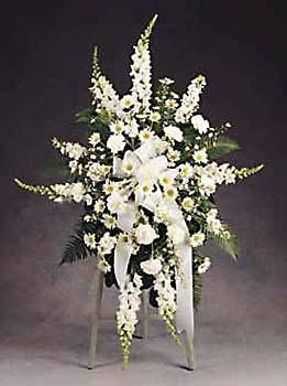 A noble tribute featuring pristine white flowers such as Carnations, Pompons, Monte Casino, Snapdragons, Stock, and elegant greens accented with a white ribbon.