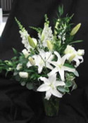Our Churchill arrangement is a lovely vase of Oriental Lilies in white, Snapdragons, white Escimo roses , white Alstroemeria, mixed foliage.Hatcher original. Styled in a glass vase. Send to the funeral home, or residence
