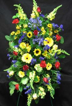Enlongated spray of bright coloured flowers. A prestigious piece of flowers for family or a close friend