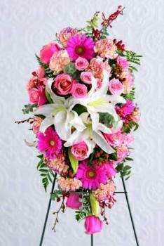 Beautiful standing spray of three white Oriental lilies surrounded by pink Gerbera daisies, pink roses, variegated pink carnations and orchids.We deliver to all Toronto and area funeral homes.