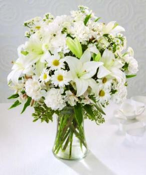 The innocence of a child is reflected in this arrangement of pure white flowers. All white carnations, alstroemeria, daisy and button poms and lilies are lovingly designed in a clear glass vase.