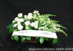 A gentle flow of white snapdragons, white roses, white carnations, mixed foliage and a banner. Roughly 50-60 cm long. Express your sympathy with this all white arrangement. We can custom inscribe  a banner for you.
