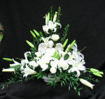 An Angel figurine nestled amongst a stunning white combination of white Escimo roses, Siberia oriental lilies, and mixed foliages. We deliver to Kane, Jerrett, Simple Alternative, Newbigging, Trull, and Humprey Funeral homes. We also service all the other homes in Toronto, and the GTA. Hatcher original design.