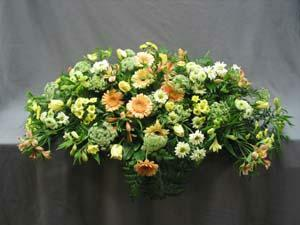 A full casket spray of peach Gerbera, yellow, white, and peach Alstroemeria, Versillia Roses, white and yellow Daisies, Queen Anne's Lace, and mixed foliage. This is for a closed casket.