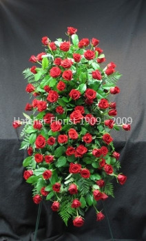 A beautiful red standing spray with 5 dozen Freedom eco roses.  A stunning piece from the family. We can use other cours of roses.