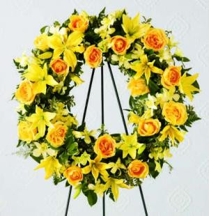 This beautiful wreath holds golden yellow roses, Asiatic lilies and alstroemeria against a background of assorted greenery. An expression of your friendship and sympathies.