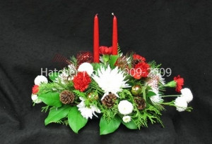 A lovely centrepiece with two red candles, seasonal greenery, mixed red and white flowers, seasonal fragrant pine, fir and pine cones.