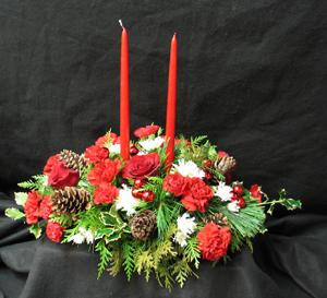 Hatcher's Traditional Centrepiece comes complete with two red tapers, fragrant Pine, Fir, Cedar, Cones, red Carnations, white Starburst Chrysanthemus, red glass balls, Holly, and red Roses. Deck the halls, or table with this beauty.