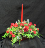 Centerpiece with B C Holly, seasonal Douglas fir, Cedar, White pine, red Freedom, Roses, red Miniature carnations, a red 15 inch candle, gold balls and pine cones.